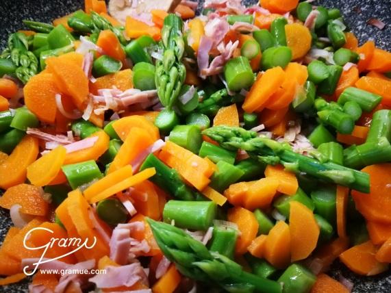 Spargel, Karotten und Schinken in einer Pfanne anrösten